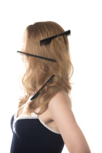 Young blond woman with three combs stuck in her tangled hair, studio isolated portrait on white background